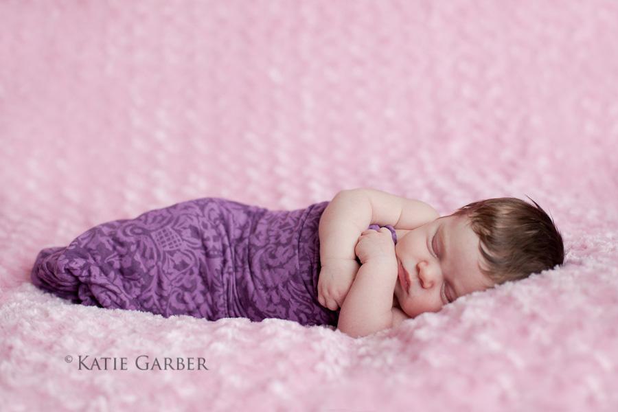 baby girl sleeping on pink blanket