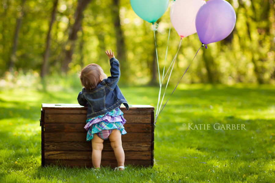 baby girl looking at balloons